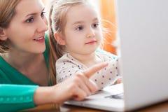 Κόρη και μητέρα που εξετάζουν ένα lap-top στοκ φωτογραφία