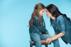 Κόρη και μητέρα που εξετάζουν η μια την άλλη στο στούντιο στο μπλε στοκ εικόνα