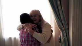 Κόρη και μητέρα στα έτη που αγκαλιάζουν εσωτερικό καλό φιλμ μικρού μήκους