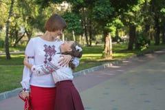 Κόρη και mom στάση και αγκάλιασμα στα κεντημένα πουκάμισα Στοκ φωτογραφία με δικαίωμα ελεύθερης χρήσης