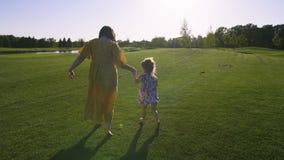 Κόρη και mom τρέξιμο στο πράσινο λιβάδι χλόης απόθεμα βίντεο
