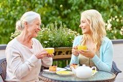 Κόρη με το ανώτερο τσάι κατανάλωσης μητέρων στον καφέ Στοκ Εικόνα
