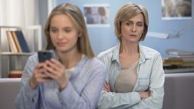 Κόρη με το smartphone στα χέρια που αγνοεί το mom της, αδιαφορία, ηλικία εφηβείας απόθεμα βίντεο