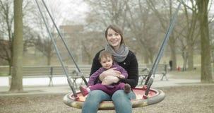 Κόρη μητέρων και μωρών που έχει τη διασκέδαση σε μια ταλάντευση από κοινού απόθεμα βίντεο