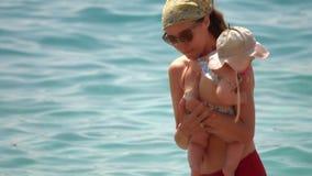 Κόρη μητέρων και μωρών στα όπλα της στην παραλία στοκ εικόνα