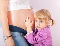 Κόρη που αγκαλιάζει την έγκυο κοιλιά της μητέρας Στοκ Εικόνα