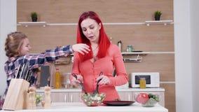 Κόρη που αγκαλιάζει τη μητέρα της ενώ κάνει τη σαλάτα στην κουζίνα απόθεμα βίντεο