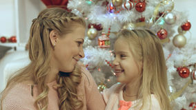 Κόρη που αγκαλιάζει και που φιλά τη μητέρα της κοντά στο χριστουγεννιάτικο δέντρο Στοκ Φωτογραφίες