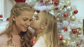 Κόρη που αγκαλιάζει και που φιλά τη μητέρα της κοντά στο χριστουγεννιάτικο δέντρο Στοκ εικόνες με δικαίωμα ελεύθερης χρήσης