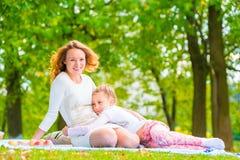 Κόρη που αγκαλιάζει τη μητέρα της στο χορτοτάπητα Στοκ φωτογραφία με δικαίωμα ελεύθερης χρήσης