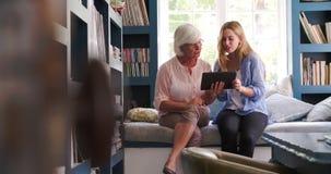 Κόρη που βοηθά την ανώτερη μητέρα με την ψηφιακή ταμπλέτα στο σπίτι απόθεμα βίντεο