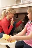 Κόρη που βοηθά τη μητέρα για να εκκαθαρίσει την έχουσα διαρροή καταβόθρα στοκ φωτογραφίες