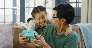 Κόρη που δίνει το κιβώτιο δώρων στον πατέρα στο καθιστικό 4k απόθεμα βίντεο