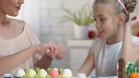 Κόρη που επιλέγει το ρόδινο αυγό στα χέρια μητέρων, οικογενειακό παιχνίδι στα παιχνίδια Πάσχας απόθεμα βίντεο