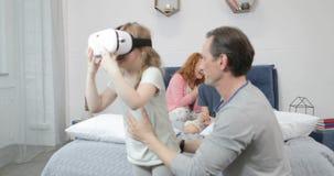 Κόρη που δοκιμάζει τα γυαλιά εικονικής πραγματικότητας με τον πατέρα στην κρεβατοκάμαρα, οικογενειακό πρωί μαζί στο σπίτι απόθεμα βίντεο