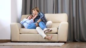 Κόρη που τρέχει μέσω της μητέρας της που κάθεται στον καναπέ απόθεμα βίντεο