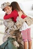 Κόρη που χαιρετά το στρατιωτικό σπίτι μητέρων στην άδεια στοκ εικόνα