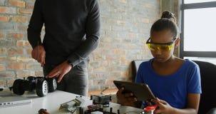 Κόρη που χρησιμοποιεί την ψηφιακή ταμπλέτα ενώ πατέρας που επισκευάζει το ηλεκτρικό αυτοκίνητο 4k απόθεμα βίντεο