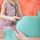 Κόρη που χρησιμοποιεί το λευκό στηθοσκοπίων που εξετάζει την έγκυο μητέρα Στοκ Φωτογραφία