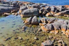Κόλπος των πυρκαγιών Τυρκουάζ νερά με την πορτοκαλιά ανάπτυξη λειχήνων στο gra Στοκ Εικόνες