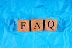 Κύβοι με μια επιγραφή FAQ σε τσαλακωμένο μπλε χαρτί Στοκ Εικόνες