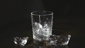 Κύβοι πάγου που καταβρέχουν στο νερό πέρα από το λευκό φιλμ μικρού μήκους