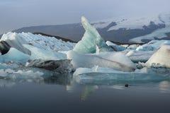 Κύβοι πάγου στη λιμνοθάλασσα παγετώνων Jokulsarlon με τη σειρά βουνών χιονιού Στοκ Εικόνες