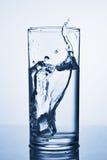 Κύβος πάγου που πέφτουν στο ποτήρι του νερού στοκ εικόνες με δικαίωμα ελεύθερης χρήσης