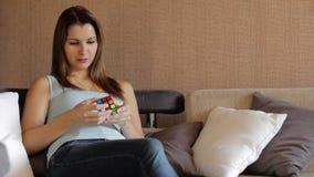 Κύβος Rubik ` s Όμορφα παιχνίδια γυναικών με έναν κύβο Rubik ` s Το κορίτσι προσπαθεί να συγκεντρώσει έναν κύβο Rubik ` s η γυναί φιλμ μικρού μήκους