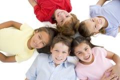 κύκλος πέντε φίλοι που χαμογελούν τις νεολαίες Στοκ φωτογραφία με δικαίωμα ελεύθερης χρήσης