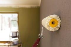 Κύλινδρος για τη ζωγραφική ενάντια στον γκρίζο τοίχο Κάδος σκαλών και χρωμάτων στο υπόβαθρο Στοκ Φωτογραφία
