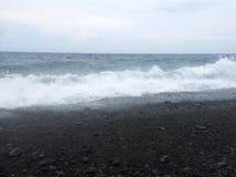 Κύματα, αφρός κυματωγών και θάλασσας που χτυπά την αμμώδη μαύρη ηφαιστειακή παραλία άμμου του Μπαλί Σε Amed, η θάλασσα είναι ήρεμ στοκ εικόνες
