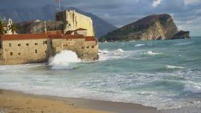 Κύματα θάλασσας άποψης στην παραλία, παλαιά πόλη Budva στο υπόβαθρο απόθεμα βίντεο