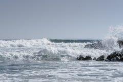 Κύματα θάλασσας που συντρίβουν στους βράχους παραλιών με τον απλό ορίζοντα και το σαφή ουρανό Καταβρέχοντας κύματα στην παραλία Στοκ εικόνες με δικαίωμα ελεύθερης χρήσης