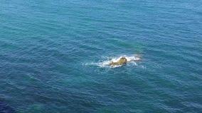 Κύματα θάλασσας που συντρίβουν στο σκόπελο απόθεμα βίντεο