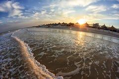 Κύματα θάλασσας που κυλιούνται στην αμμώδη ακτή όμορφο ηλιοβασίλεμα Στοκ Φωτογραφίες