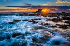 Κύματα και βράχοι στο ηλιοβασίλεμα, σε λίγη παραλία κορώνας Στοκ Εικόνα