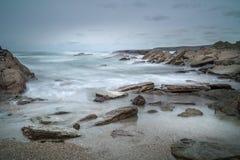Κύματα πέρα από τους βράχους, παραλία Porth, Κορνουάλλη στοκ φωτογραφία με δικαίωμα ελεύθερης χρήσης