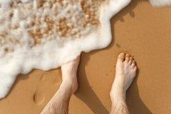 Κύματα που κτυπούν ενάντια στα πόδια στην παραλία Στοκ Εικόνες