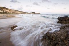 Κύματα που πλένουν πέρα από έναν βράχο στο ηλιοβασίλεμα Στοκ εικόνες με δικαίωμα ελεύθερης χρήσης