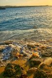 Κύματα που σπάζουν στην παραλία άμμου στο ηλιοβασίλεμα στοκ εικόνες