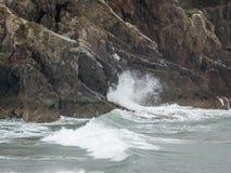 Κύματα που σπάζουν στον απότομο βράχο Στοκ Φωτογραφίες