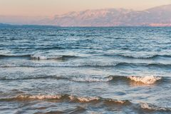 Κύματα που συντρίβουν επάνω στην παραλία στο ηλιοβασίλεμα με τα χιονισμένα βουνά στο υπόβαθρο Στοκ Εικόνα