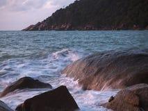 Κύματα που συντρίβουν στις παράκτιες πέτρες στην ανατολή στοκ εικόνες
