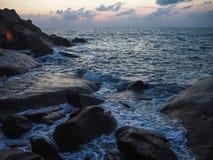 Κύματα που συντρίβουν στις παράκτιες πέτρες στην ανατολή στοκ φωτογραφία