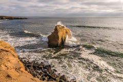 Κύματα που συντρίβουν στο βράχο πουλιών στους απότομους βράχους ηλιοβασιλέματος Στοκ εικόνα με δικαίωμα ελεύθερης χρήσης