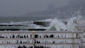 Κύματα που συντρίβουν στο κιγκλίδωμα αποβαθρών που καλύπτεται με τον πάγο στοκ εικόνα
