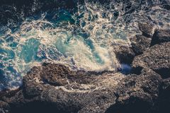 Κύματα που συντρίβουν το σπάσιμο στους βράχους Εναέρια άποψη επιφάνειας θάλασσας κηφήνων Στοκ εικόνα με δικαίωμα ελεύθερης χρήσης