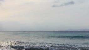 Κύματα σε μια παραλία χαλικιών το βράδυ νεφελώδες με το κρουαζιερόπλοιο και τα βουνά στον ορίζοντα φιλμ μικρού μήκους
