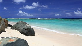 Κύματα σε μια τροπική παραλία με τους βράχους φιλμ μικρού μήκους